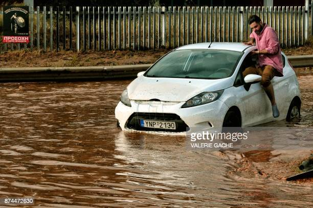 A man tries to get into a car stuck in floodwater in the town of Mandra northwest of Athens on November 15 after heavy overnight rainfall in the area...