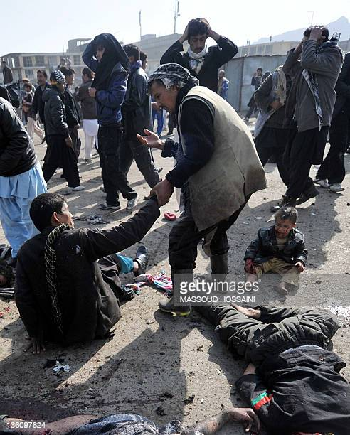 A man tries to help a bombing victim moments after a suicide bomber killed dozens after detonating a bomb during a religious ceremony in Kabul on...