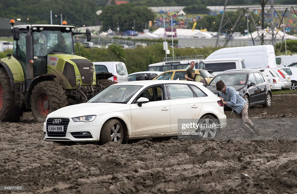 A man tries to push a car as festival goers leave the Glastonbury Festival 2016 at Worthy Farm, Pilton on June 26, 2016 near Glastonbury, England. The Festival, which Michael Eavis started in 1970 when several hundred hippies paid just £1, now attracts more than 175,000 people.