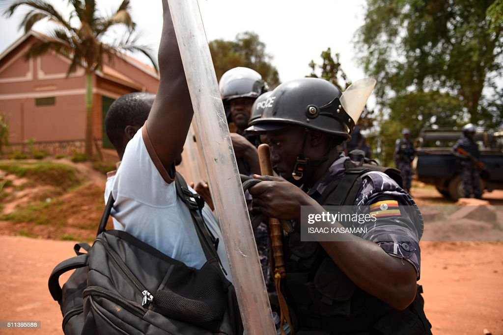 TOPSHOT - A man tries to push past police officers guarding the drive way to the home of opposition leader, Kizza Besigye, in Kasangati, a Kampala suburb on February 20, 2016. Uganda's top presidential challenger Kizza Besigye was arrested on February 19, 2016, for a third time in a week. Police escorted him home, where he remained the day after with security forces surrounding his house, saying they wanted to prevent him from unilaterally proclaiming his vote score. Besigye called for a press conference on February 20, 2016, but journalists were denied access to his home. / AFP / Isaac Kasamani