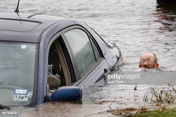 A man tries to rescue a car that was swept away by flood water caused by Hurricane Ike while trying to evacuate Galveston Island September 12 2008 in...