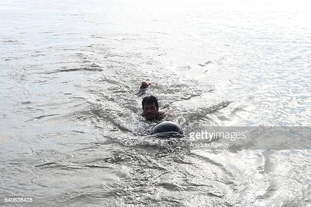 A man tries to rescue a short fin pilot whale which washed up on Randu Pitu village beach on June 16 2016 in Probolinggo East Java Province Indonesia...