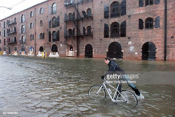 A man tries to ride his bike through flood waters on Van Brunt Street in Red Hook Brooklyn Monday morning as Hurricane Sandy slowly makes her way to...