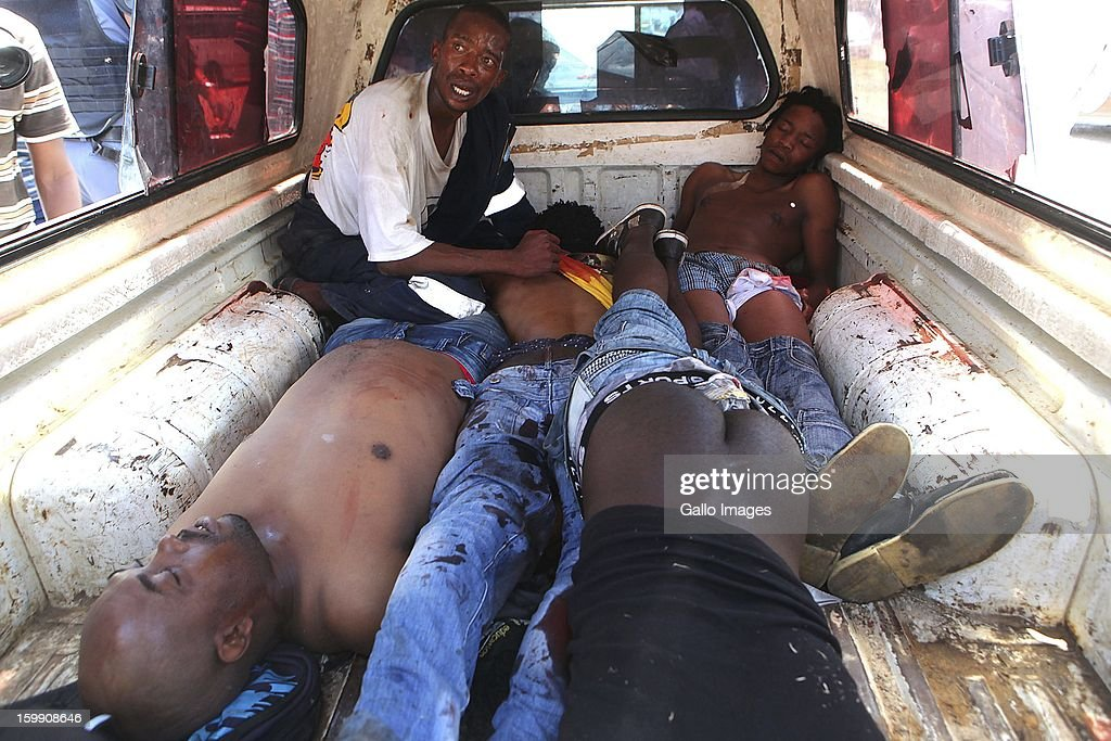 A man tries to rush dead and injured protestors to hospital on January 22, 2013, in Sasolburg, South Africa. The announcement of government's intention to merge municipalities in the Free State sparked outrage in Zamdela township residents.