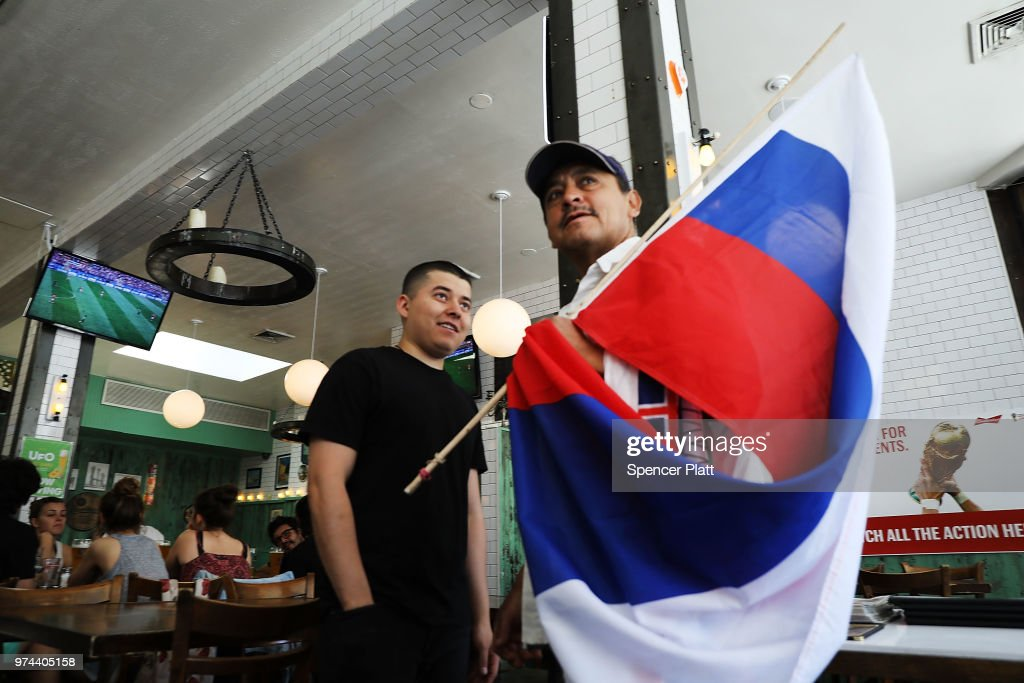 A man tries to sell a Russian flag during the opening soccer match of the 2018 FIFA World Cup at Cafe Max in Russian enclave Brighton Beach June 14, 2018 in the Brooklyn borough of New York City. The 2018 World Cup, one the world's premier sporting events, is being hosted by Russia this year as the country looks to improve its relations with the West.