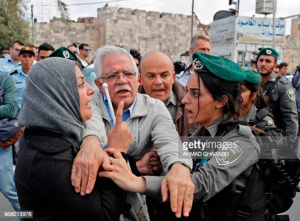 A man tries to separate a Palestinian woman and an Israeli border guard confronting themselves at Damascus gate in Jerusalem on May 13 as Israeli...
