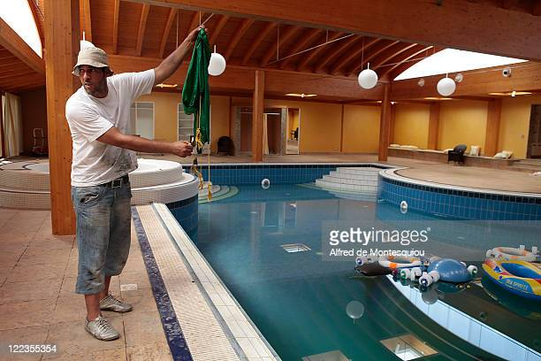 A man tries to set fire to a Gaddafi flag found in the vast indoor pool on the compound of Aisha Gaddafi's luxury villa on August 27 2011 in Tripoli...
