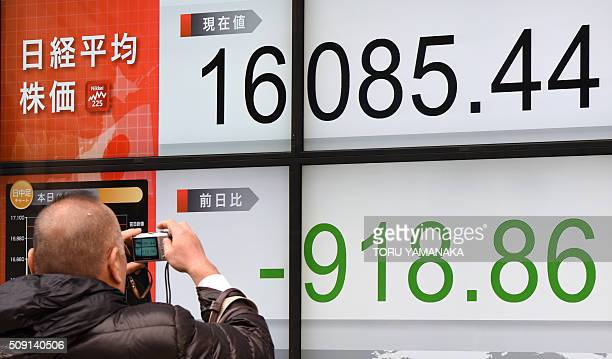 A man tries to take pictures of an electric quotation board flashing the Nikkei key index of the Tokyo Stock Exchange in front of a securities...