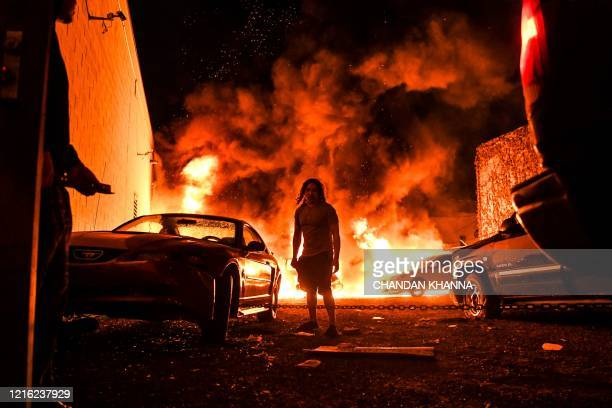 Man tries to tow away a car in a safe zone as the other car catches fire in a local parking garage on May 29, 2020 in Minneapolis, Minnesota, during...