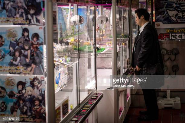 A man tries to win a toy at a game machine in Akihabara Electric Town on May 20 2014 in Tokyo Japan Akihabara gained the nickname Akihabara Electric...