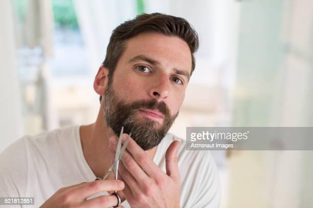Man trimming beard in bathroom