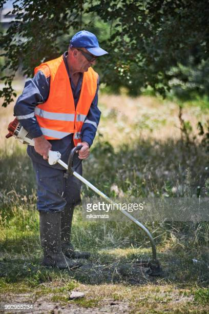 Man Trims Grass in Safety Equipment