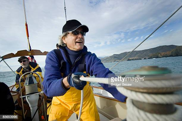 A man trims the sails on his yacht.