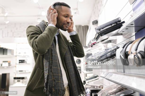 man trying headphones in a store - electrical equipment stock pictures, royalty-free photos & images