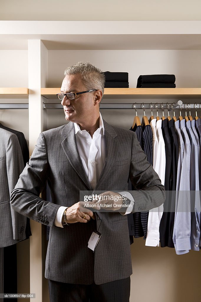 Man trying on blazer at clothing store : Foto stock