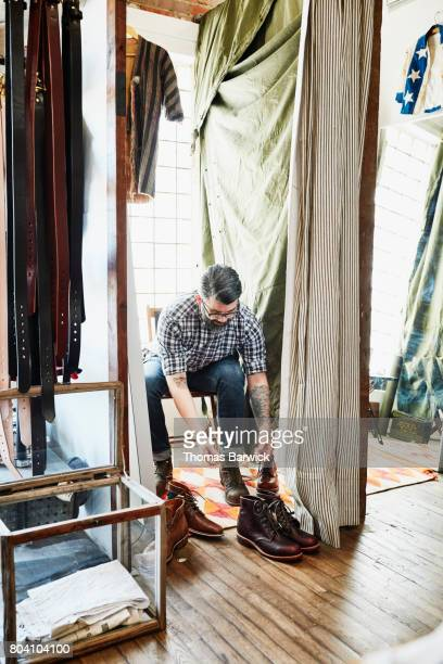 Man trying on boots in mens boutique