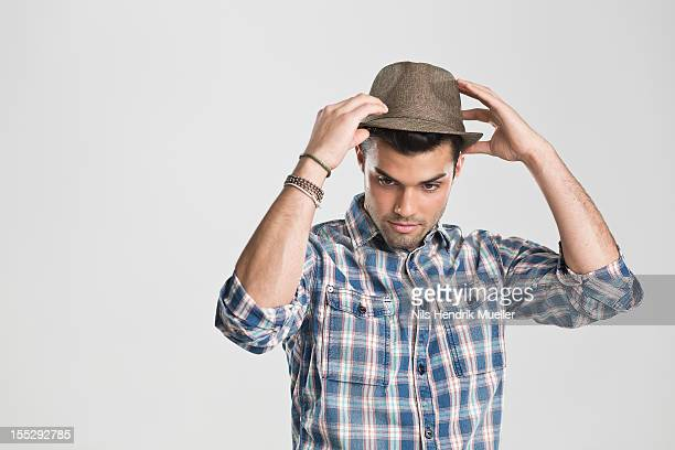man trying on hat - fedora stock pictures, royalty-free photos & images
