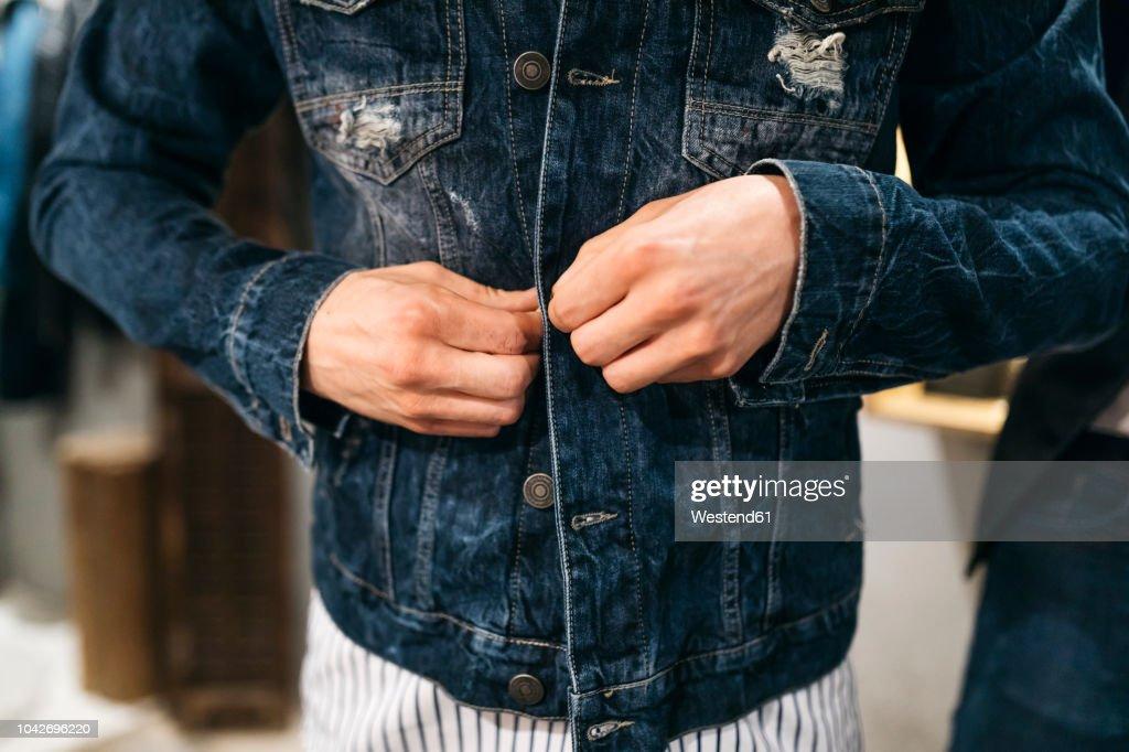 Man trying on new denim jacket : Stock Photo