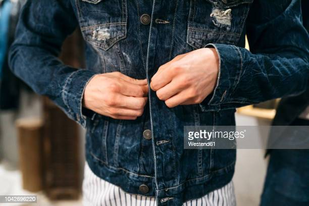 man trying on new denim jacket - giacca foto e immagini stock