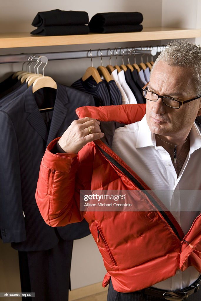 Man trying on red coat at clothing store : Foto stock