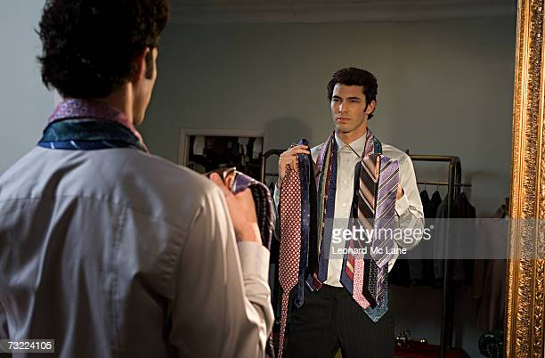 Man trying on tie, standing in front of mirror