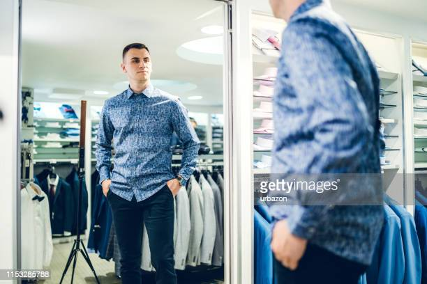 man trying shirt in a store - fitting room stock pictures, royalty-free photos & images