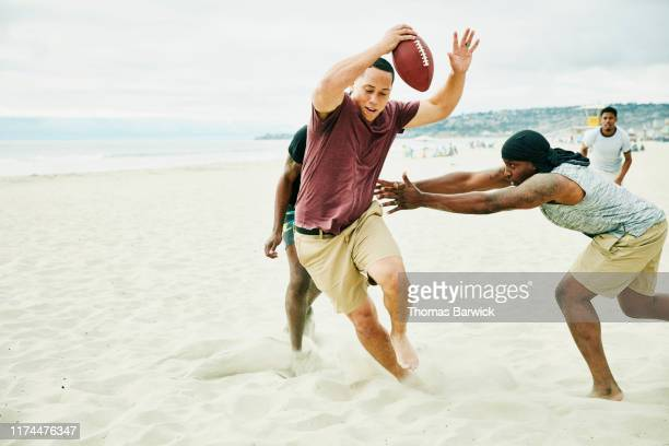 man trying to avoid defenders during touch football game on beach - rush fútbol americano fotografías e imágenes de stock