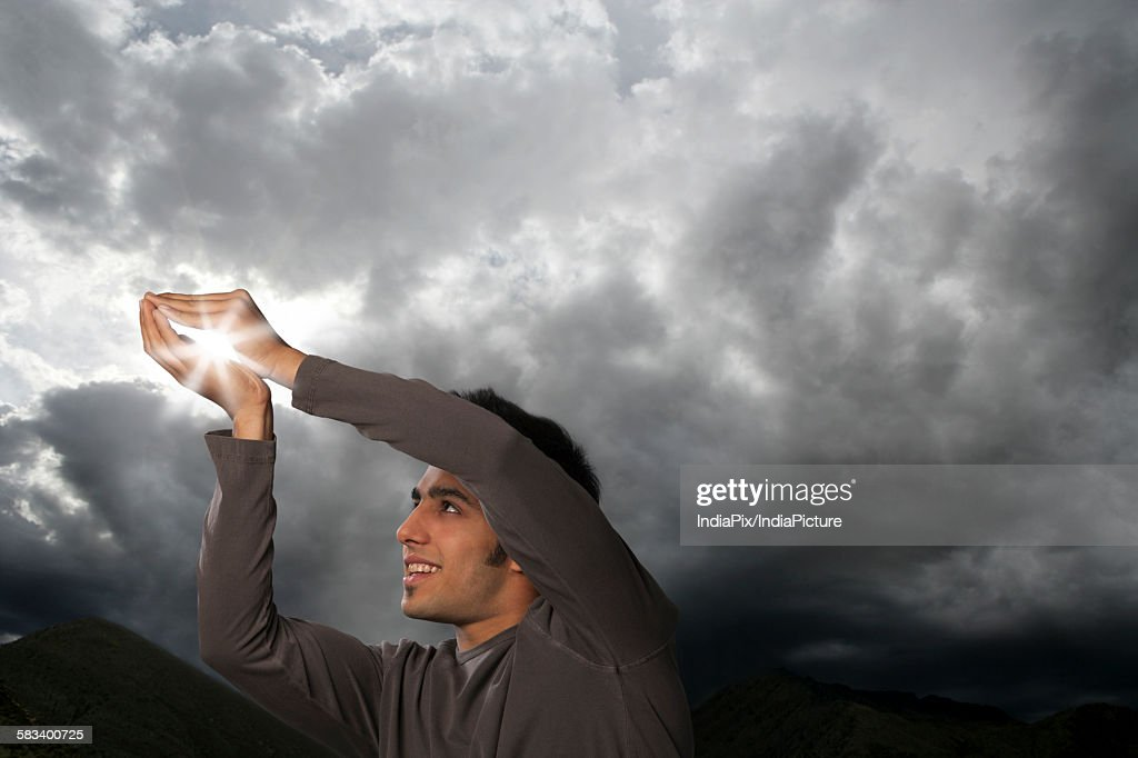 Man trying to catch sun rays : Stock Photo