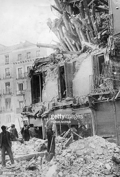 A man trying to clear away the wreckage of a building at Madrid after bombing by rebel forces