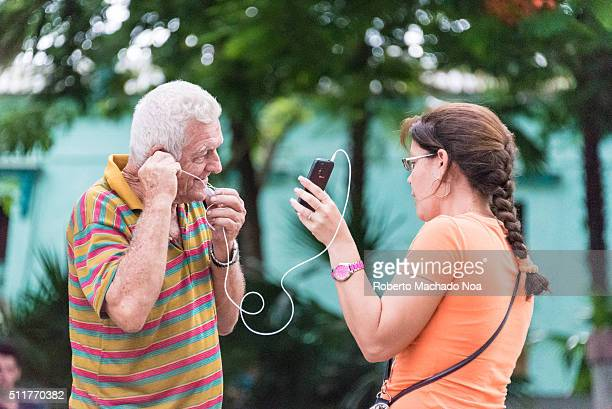 Man trying to connect to call A lady is helping an old man in connecting call Using headphone they are talking to someone Cuban people in public...