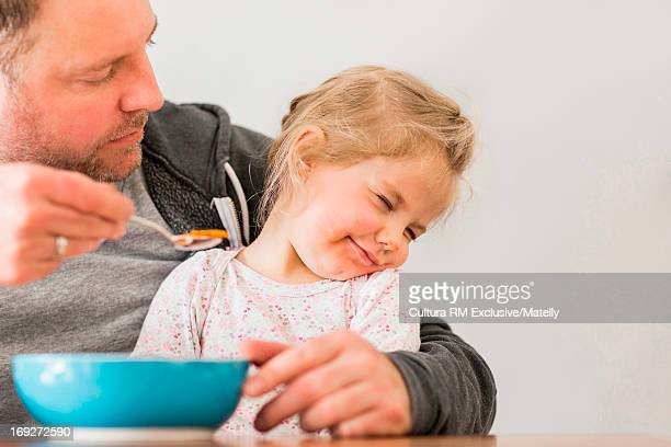 Man trying to feed girl but she is refusing