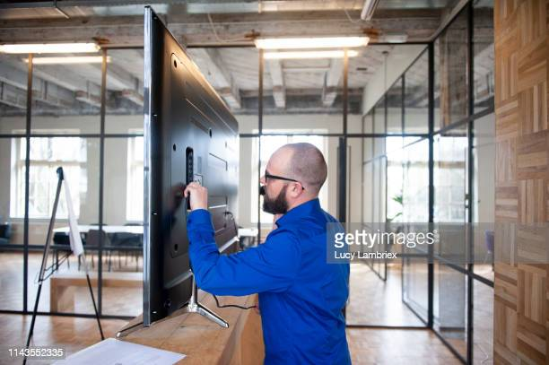 man trying to get the monitor to work for his presentation - installing stock pictures, royalty-free photos & images