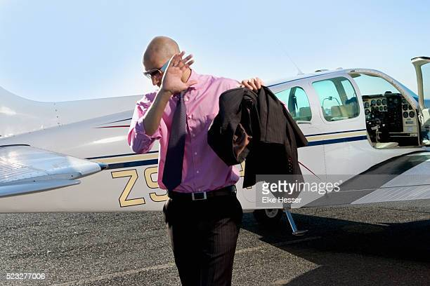 man trying to hide his face in front of airplane - best sunglasses for bald men stock pictures, royalty-free photos & images