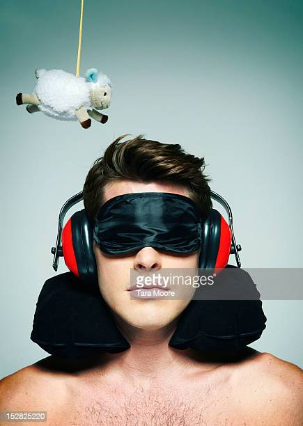 man trying to sleep with sheep and sleeping mask