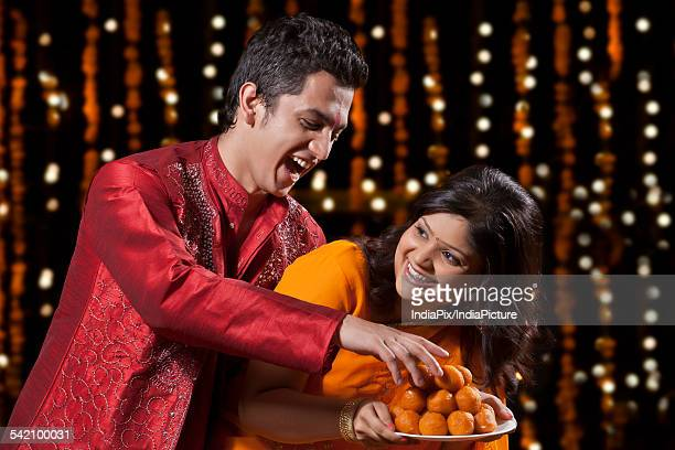 man trying to take sweets from woman - mithai stock pictures, royalty-free photos & images