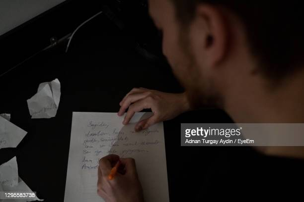 man trying to write something,wads of paper, struggling with writer's block. - the_writer's_block stock pictures, royalty-free photos & images