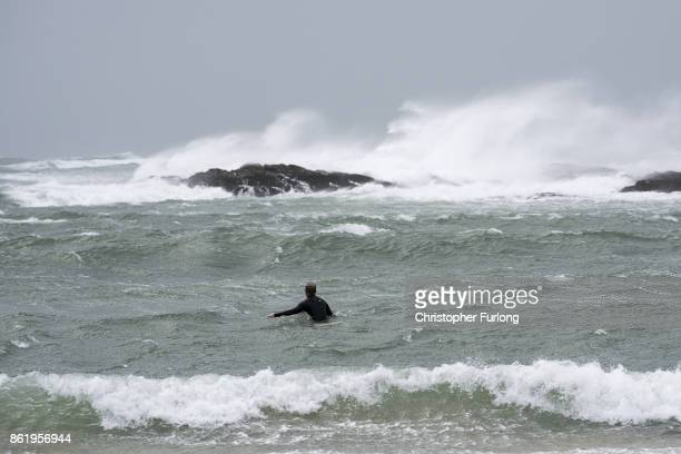 A man trys to surf in the winds of Hurricane Ophelia at Trearddur Bay on October 16 2017 in Holyhead Wales Hurricane Ophelia comes exactly 30 years...