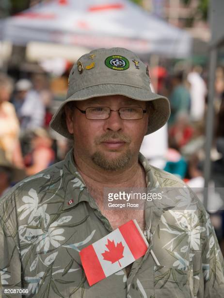 A man tucks the Canadian maple leaf flag into his shirt during Canada Day festivities in this 2008 Penticton British Columbia Canada summer photo...