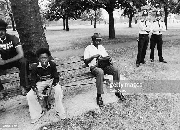 A man tuning his radio in West Ham Park East London while waiting to watch a cricket match between the local police force and West Indians 3rd August...