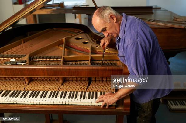 Man tuning upright piano in workshop.