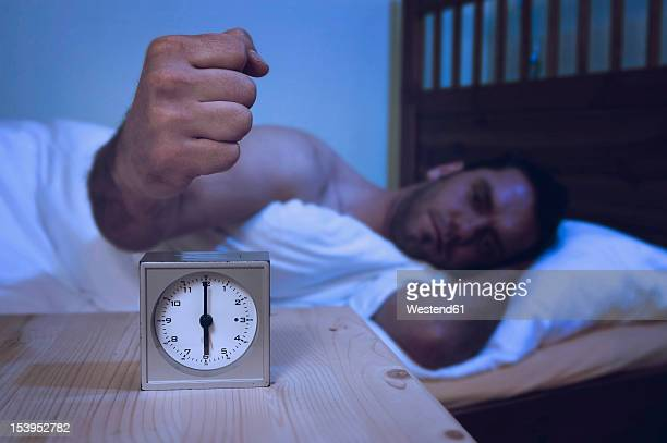 Man turning off alarm clock with fist