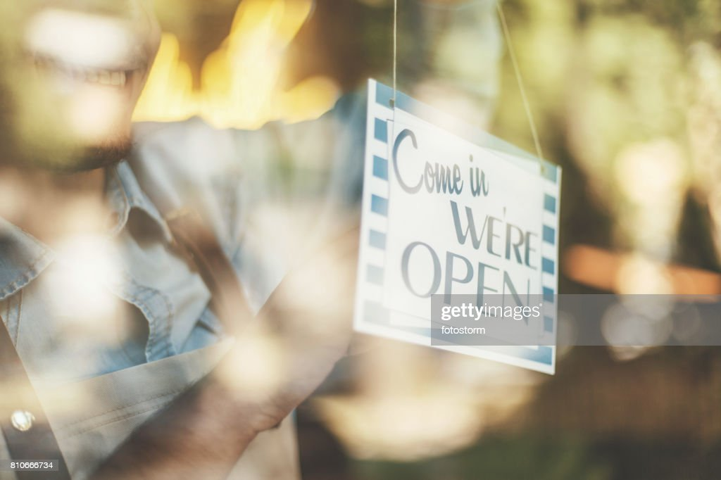 Man turning opening sign on door coffee shop : Stock Photo