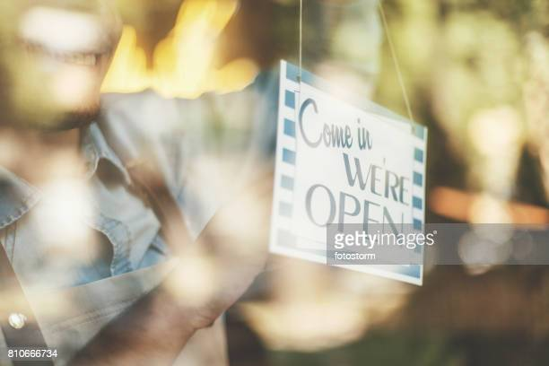 man turning opening sign on door coffee shop - opening event stock pictures, royalty-free photos & images