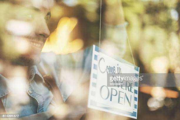 Man turning opening sign on door