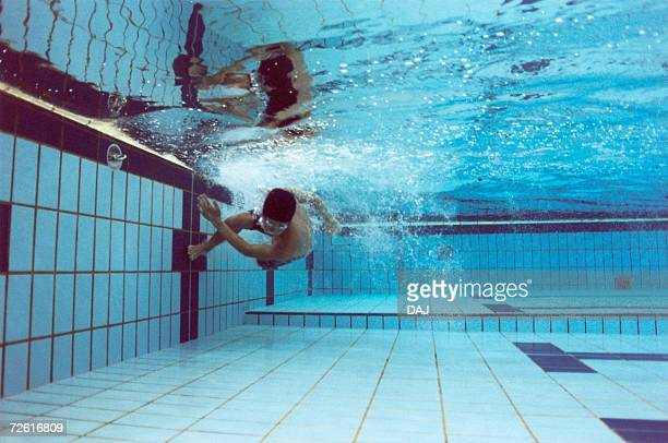 Man turning over underwater, low angle view