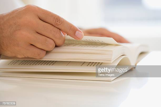 Man turning page of book