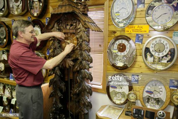 A man turning the hour hand on a Black Forest cuckoo clock at Frankenmuth Clock Company