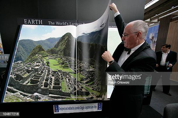 A man turns a page of the world's largest book at the Millenium House publishers stand during the Frankfurt Book Fair 2010 on October 6 2010 in...