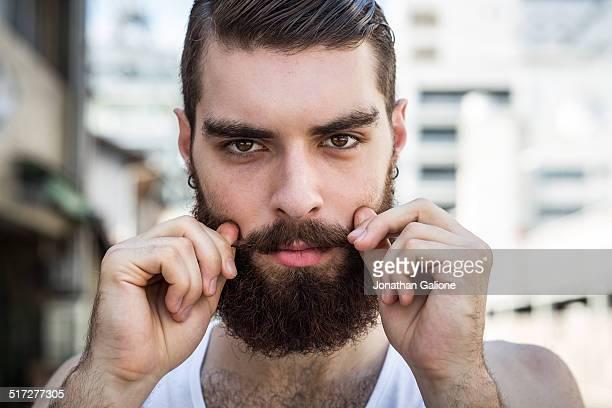 man twisting his mustache into shape - オールバック ストックフォトと画像