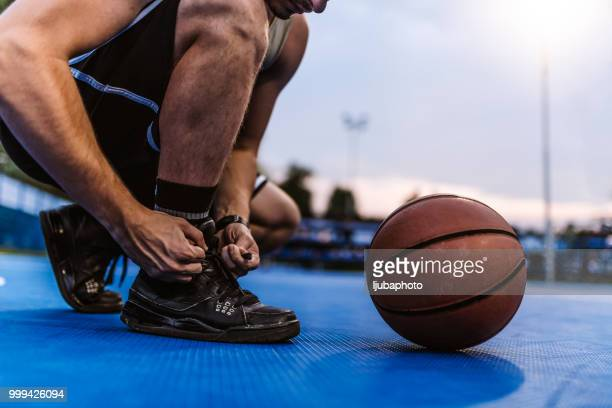 man tying his shoe laces on a basketball court - basketball shoe stock photos and pictures
